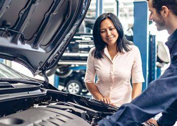mulher de semblante tranquilo conversando com o mecânico que está consertando seu carro